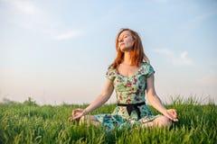 Ładna kobieta medytuje w parku Obrazy Royalty Free