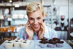 Ładna kobieta patrzeje filiżanka torty Fotografia Royalty Free