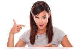 Ładna latynoska kobieta wskazuje jej palma up Zdjęcia Royalty Free