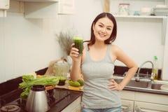 ?adna m?oda kobieta pije jarzynowego smoothie w jej kuchni obraz royalty free