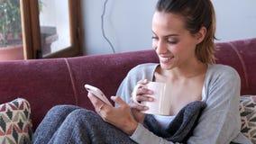 ?adna m?oda kobieta u?ywa jej telefon kom?rkowego podczas gdy pij?cy kaw? na kanapie w domu zdjęcie wideo