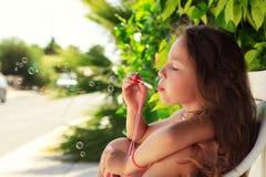 Ładna mała dziewczynka dmucha mydlanych bąble plenerowych przy zmierzchem - szczęśliwy beztroski dzieciństwo Fotografia Stock