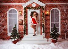 Ładne kobiety plenerowe w czerwieni ubraniach Santa Obrazy Royalty Free