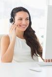 Ładnego centrum telefonicznego faktorski obsiadanie przy jej biurkiem na wezwaniu Zdjęcia Royalty Free
