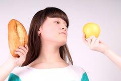 Ładny dziewczyny mienie i zjadliwy bochenek chleb Obrazy Stock