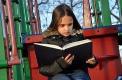 Ładny Latynoski dziewczyny czytanie przy boiskiem zdjęcie stock