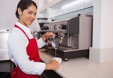 Ładny młody barista dolewania mleko w filiżankę kawy ono uśmiecha się przy kamerą Zdjęcie Stock
