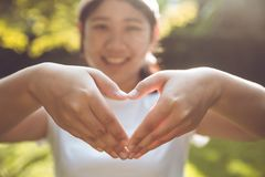 Ado asiatique mignon avec le signe d'amour de main Photos stock