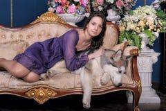 Ado de fille et malamute de chien sur le sofa Photo stock
