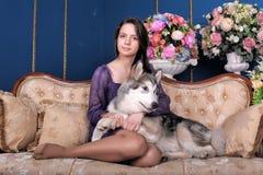 Ado de fille et malamute de chien sur le sofa Images libres de droits