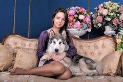 Ado de fille et malamute de chien sur le sofa Image libre de droits