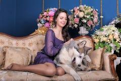 Ado de fille et malamute de chien sur le sofa Photographie stock libre de droits