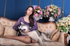 Ado de fille et malamute de chien sur le sofa Photographie stock