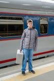 Ado de garçon avec un train proche de sac de voyage Images stock