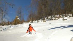 Ado marchant dans la neige profonde et tombant dans elle à la montagne banque de vidéos