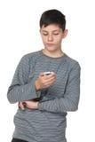 Ado réfléchi avec un téléphone portable images libres de droits