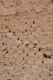 Adobe brick wall with worn-off plaster Royalty Free Stock Photo