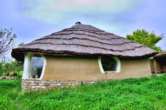 Adobe clay house with thatch. Hande made house from adobe clay dirt and roof from thatch like flintstone home stock photography