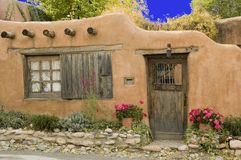 Adobe cottage. With interesting door, window and flowers in front Royalty Free Stock Image