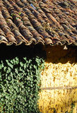 Adobe frame-build wall roof tiles. Adobe frame-build yellow wall old roof tiles stock photo