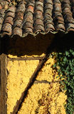 Adobe frame-build wall roof tiles. Adobe frame-build yellow wall old roof tiles green ivy stock photography