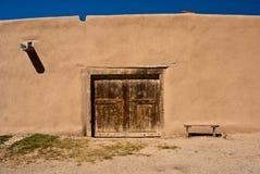 Adobe-Gebäude mit alter Tür und Bank Stockfoto