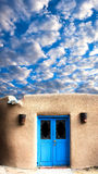 Adobe-Gebäude mit blauen Front Door Stockbilder