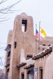 Adobe-Gebäude in Santa Fe mit Amerikaner-und New Mexiko-Flaggen Stockbilder