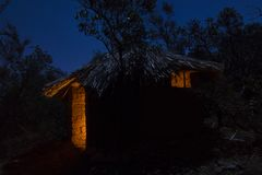 Adobe hut with thatched roof at night Stock Photos