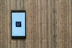 Adobe photoshop在智能手机屏幕上的lightroom商标在木背景 免版税库存照片