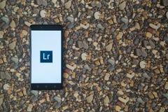 Adobe-photoshop lightroom Logo auf Smartphone auf Hintergrund von kleinen Steinen Stockbild