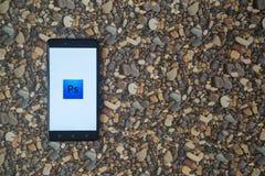 Adobe-photoshop Logo auf Smartphone auf Hintergrund von kleinen Steinen Lizenzfreie Stockbilder