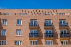 Adobe-Struktur mit Reihen von Fenstern und von Balkonen Stockfotos