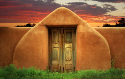 Adobe Wall with Gate. An adobe wall with wooden gate leading to a southwest sunset Royalty Free Stock Image