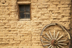 Adobe Wall. The adobe wall of old western cabin with a wagon wheel Royalty Free Stock Photography