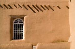 Adobe-Wand mit Fenster und Schatten Stockfoto