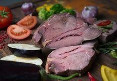 Adobo de la carne y de verduras frescas en la tabla de madera fotografía de archivo