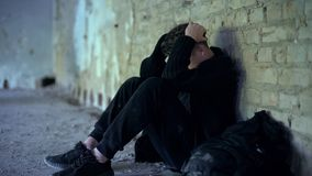 Adolescence problems, teen boy hiding in abandoned building, escape from bully. Stock photo royalty free stock image