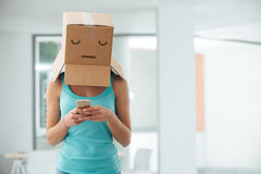 Adolescence and social isolation. Young teen girl with a box on her head texting with her mobile phone, adolescence and social isolation concept royalty free stock photography