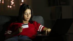 Adolescencia feliz que paga en línea con la tarjeta de crédito en la noche