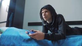 Adolescencia joven y suéter encapuchado del hombre de la palanca de mando absorbente en videojuego en línea adolescente del mucha metrajes