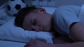 Adolescencia que duerme reservado en la cama, luces de los coches que pasan cerca, descansando después de día duro almacen de metraje de vídeo