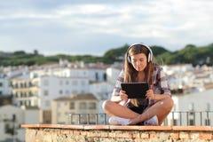Adolescencia que mira el vídeo o el aprendizaje electrónico en línea en una tableta imagenes de archivo