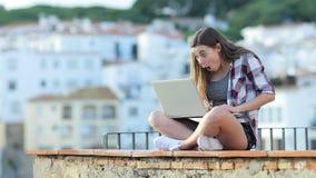 Adolescencia sorprendida que encuentra el contenido que sorprende en un ordenador portátil almacen de video
