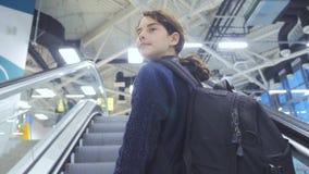 Adolescencia turística de la chica joven con la mochila con la maleta para arriba abajo de la escalera móvil el aeropuerto que es metrajes