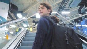 Adolescencia turística de la chica joven con la mochila con la maleta para arriba abajo de la escalera móvil el aeropuerto que es almacen de metraje de vídeo