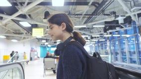 Adolescencia turística de la chica joven con la mochila con la maleta para arriba abajo de la escalera móvil la forma de vida del almacen de metraje de vídeo