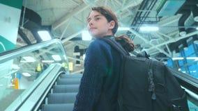 Adolescencia turística de la chica joven con la mochila con la maleta para arriba abajo de la escalera móvil la forma de vida que almacen de metraje de vídeo