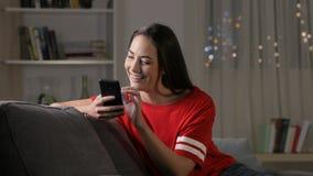 Adolescencia usando el teléfono elegante en la noche en un sofá
