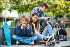 Adolescencias activas que juegan en smarthphones y que escuchan la música Fotografía de archivo libre de regalías